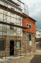 Old house with stone wall and scaffolding for refurbishment