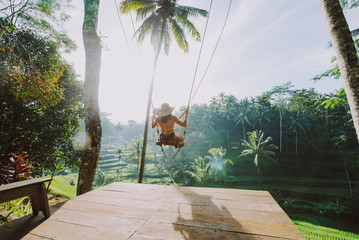 Beautiful girl visiting the Bali rice fields in tegalalang, ubud. Using a swing over the jungle. Concept about people, wanderlust traveling and tourism lifestyle 壁紙(ウォールミューラル)