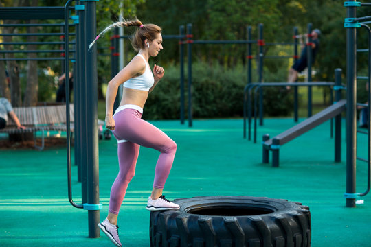 Young woman is training on the outdoor playground. Crossfit and fitness workout outdoors.