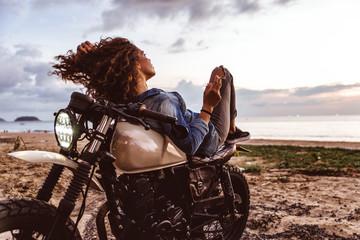 Beautiful girl having fun driving her custom cafe racer motorcycle, enjoying the sunset on the beach Fototapete