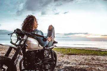 Beautiful girl having fun driving her custom cafe racer motorcycle, enjoying the sunset on the beach Wall mural
