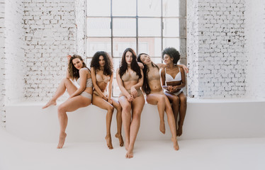 Group of women with different body and ethnicity posing together to show the woman power and strength. Curvy and skinny kind of female body concept Wall mural