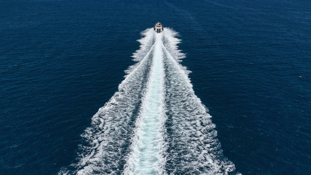 Aerial photo of inflatable rib speed boat cruising in high speed deep blue sea of Mykonos island, Cyclades, Greece