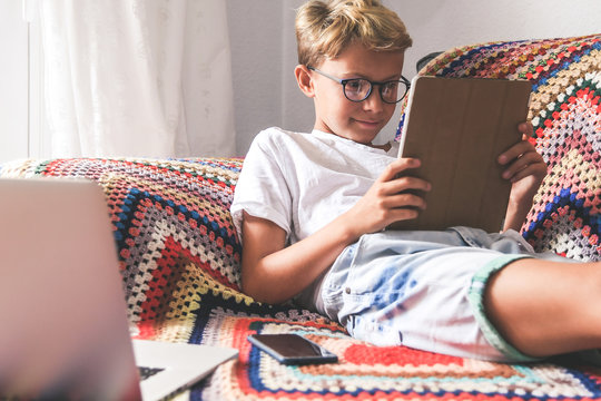 Beautiful smiling teen reading new trend stories online on tablet. Technology addicted young boy watching social video at home. Teenager communicate with generation z remote friend Youth tech concept