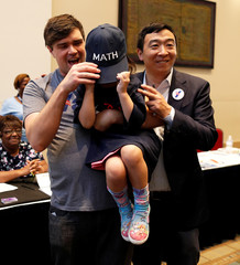 A child hides his face during a photo opportunity with Democratic presidential candidate and Silicon Valley businessman Andrew Yang at the SC Democratic Convention in Columbia