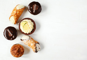 Different pastries on white background: cannoli with ricotta, tartlets filled with citrus cream, fudge cake, tiramisu cake.