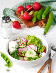 Spring vegetable salad with radish, cucumber and green peas