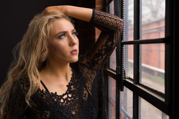A beautiful young blond woman in a lace top and bralette gazes thoughtfully and sadly out a dirty industrial window into an ally.