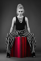 Selective color image of beautiful athletic young blond woman sitting astride a black and red striped box wearing black and white striped baggy pants and a lowcut body suit, with a stern expression