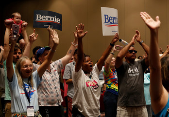 Supporters of Democratic presidential candidate Bernie Sanders hold their hands in the air during a rally for the candidate at the SC Democratic Convention in Columbia