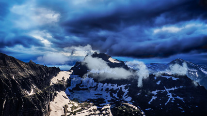 Awe Inspiring High Altitude View Of Snowy Mountain Summit Peaks And Sharp Rocky Cliffs Under Extreme Storm Clouds Summer Adventure Climb