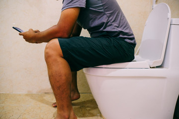 Using a mobile phone on toilet. The Asian man sitting in the toilet and working or play game in phone. Royalty high-quality free stock photo image of a man working on mobile phone while on the toilet