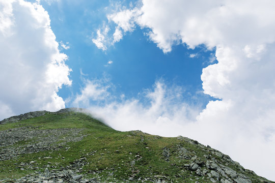 beautiful summer scenery in mountains. grassy slope with rocks. clouds on a blue sky above the mountain peak