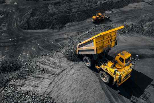 Open pit mine industry, big yellow mining truck for coal, top view aerial drone