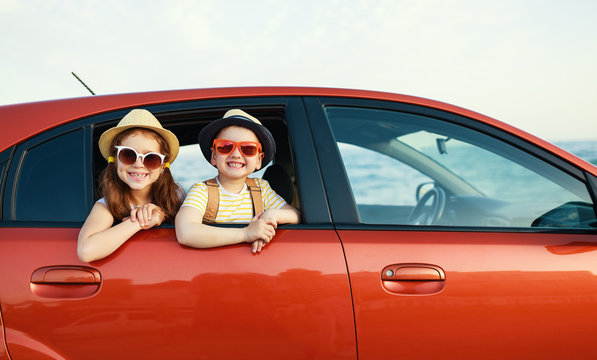 happy children girl and boy goes to summer travel trip in car.