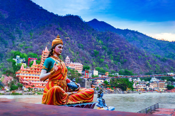 Idol of Indian God/ Goddess or deity, at the bank of river Ganga in Rishikesh with blurred temple in background , the yoga  capital of India. Indian Tourism