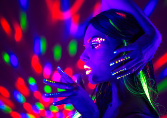 Wall Mural - Fashion disco woman. Dancing model in neon light, portrait of beauty girl with fluorescent makeup. Art design