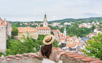 Wall Mural - Young traveler woman in hat looking at city view of Cesky Krumlov, Czech Republic in summer. Traveling europe in summer