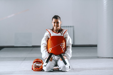 Smiling beautiful Caucasian young woman with ponytail kneeling in taekwondo fitting and looking at camera.