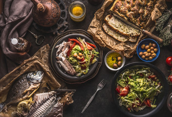 Salad bowl with backed fish and homemade bread on on dark rustic table, top view. Mediterranean lunch or dinner. Healthy food Wall mural