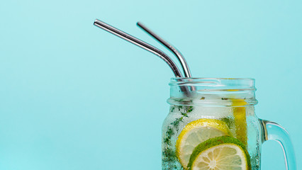 Fototapeta Cold drink in mason jar with metal straw on blue background. Lemonade or detox water with lime and thyme in glass jar with copy space for text or design. Recyclable straws, zero waste concept. Banner. obraz