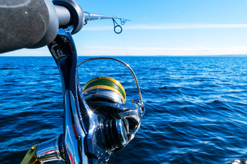 Fishing rod spinning with the line close-up. Fishing rod in rod holder in fishing boat due the fishery day. Fishing rod rings. Fishing tackle. Fishing spinning reel.