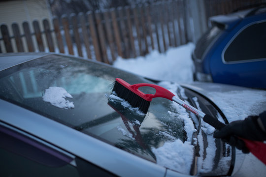 car under the snow. clean the snow with a brush. a man removes snow from the car. the guy is snowing