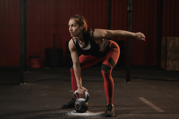 Female athlete lifting heavy weights. Sports woman holding kettlebell while crossfit training.