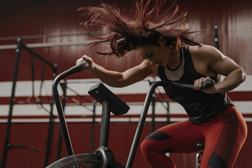Crossfit woman doing intense cardio training on exercise bike.