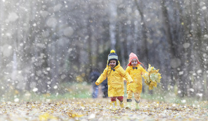 Toddlers on a walk in the autumn park. First frost and the first snow in the autumn forest. Children play in the park with snow and leaves.
