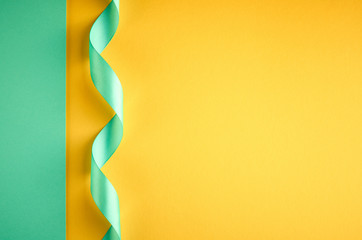 Green ribbon on green and yellow background composition, flat lay
