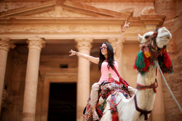 A tourist poses for a picture as she rides a camel in front of the treasury site in the ancient city of Petra, south of Amman