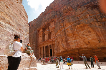 Tourists take pictures in front of the treasury site in the ancient city of Petra, south of Amman