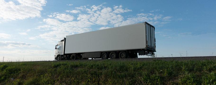 Truck driving on the asphalt road rural landscape.