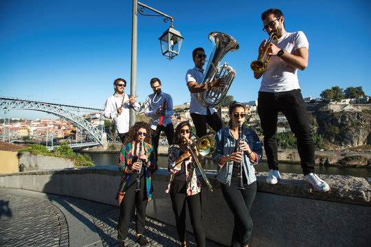 Group of Jazz musicians with wind instruments playing on the street.