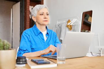 Deurstickers Ontspanning Attractive middle aged woman in blue shirt sitting in front of open portable computer having pensivelook, calculating family budget, thinking how to reduce expenses and save money for vacations