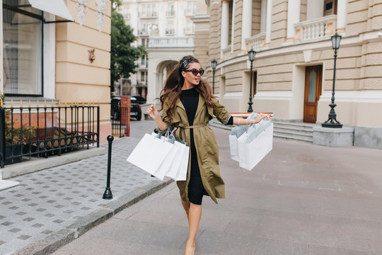 Inspired woman with long curly hair walking down the street after shopping and looking around. Outdoor photo of slim stylish lady in sunglasses carrying packages.