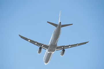 Silhouette of a climbing airliner with shiny fuselage