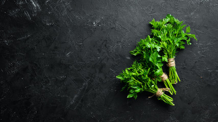 Wall Mural - Green parsley on a black stone background. Top view. Free space for your text.