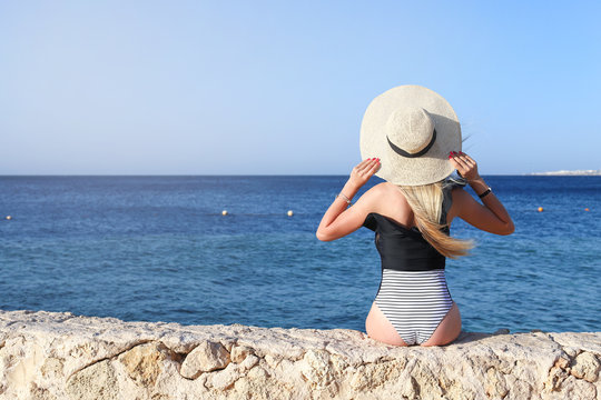 Young pretty hot sexy woman relaxing in swimsuit on stones with blue sea and sky on background. Summer Vacation Concept. Back View