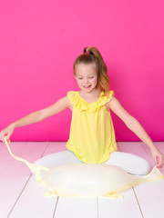 beautiful 10 year old girl is playing with yellow slime in front of pink background and is happy
