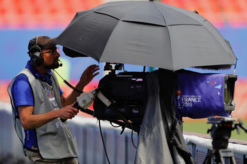 A television camera operator uses an umbrella to shelter from the sun at the side of the pitch ahead of the match between England and Cameroon during the FIFA Women's World Cup soccer tournament in Valenciennes