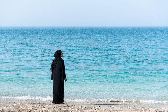 Muslim woman in abaya by the seaside