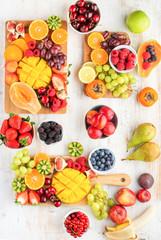 Wall Mural - Vegan breakfast, cut colorful rainbow fruits, strawberries raspberries oranges plums apples kiwis grapes blueberries mango persimmon, copy space, selective focus