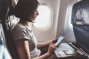 Girl using a smartphone while flying in a plane.