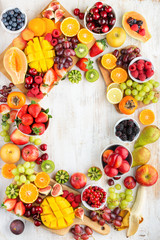Wall Mural - Healthy cut fruits frame, strawberries raspberries oranges plums apples kiwis grapes blueberries mango persimmon, on white table, copy space, top view, selective focus