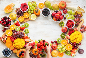 Wall Mural - Raw healthy breakfast frame, cut fruits, strawberries raspberries oranges plums apples kiwis grapes blueberries mango on white table, child's hands holding food, copy space, top view, selective focus