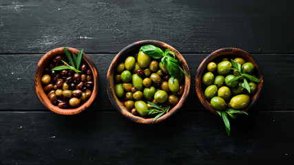 Wall Mural - Olives in a bowl, olive oil, spices and herbs. Top view. Free space for your text.