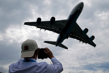 A visitor takes a picture of an Airbus A380 as it lands after an air display at the 53rd International Paris Air Show at Le Bourget Airport near Paris