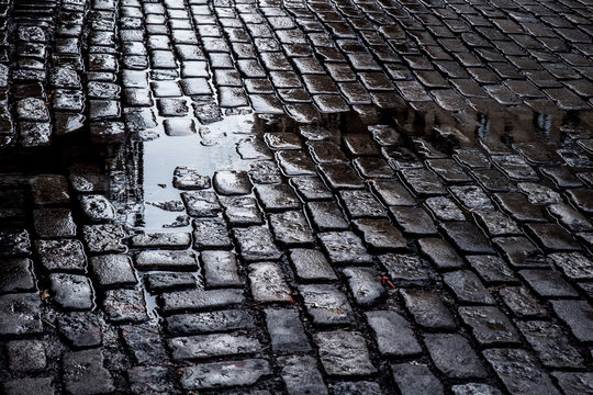 view of Grungy cobblestone street with puddles, New York City